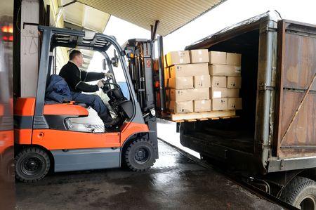 carretillas almacen: Montacargas el�ctrico en almac�n de carga de cajas de cart�n Foto de archivo