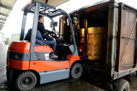 pallet truck: Electric forklift in warehouse loading cardboard boxes