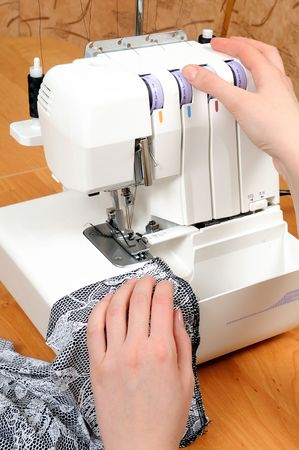 two woman hands sewing on the stichting machine photo