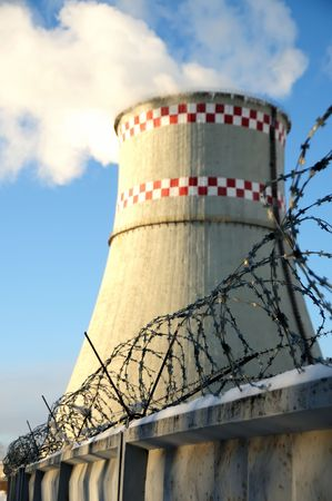 blue sky and big tube of supply station with smoke behind barbwire photo