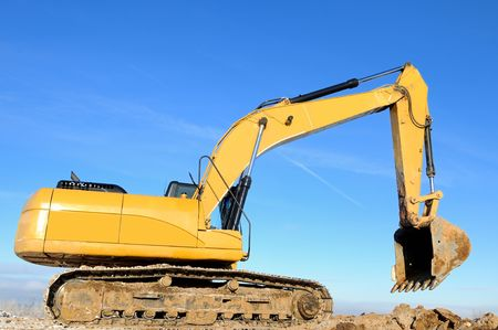 Yellow excavator loader at construction site with raised bucket over blue sky Stock Photo - 6250534