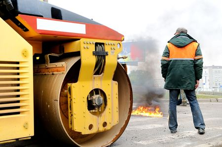 Heavy yellow roller compactor involving in fire extinguishing photo