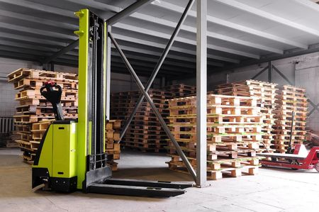 Electric forklifter stacker in warehouse in front of cardboard boxes photo