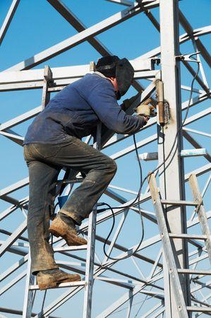 Man welder working welding with electrode outdoors photo