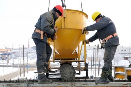 cemento: trabajadores de la construcci�n de construcci�n en la construcci�n del sitio vertiendo concreto en forma
