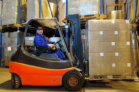 Worker driver of a forklift loader in blue workwear at warehouse with cardboard boxes on pallet Stock Photo - 6419156