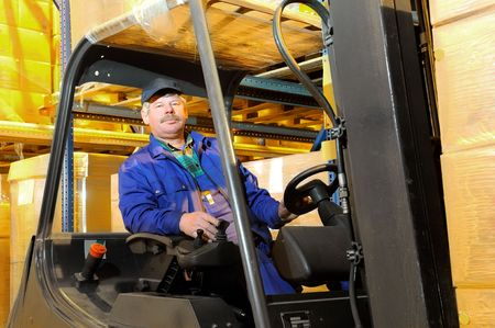 Worker driver of a forklift loader in blue workwear at warehouse with cardboard boxes on pallet Stock Photo - 6419130