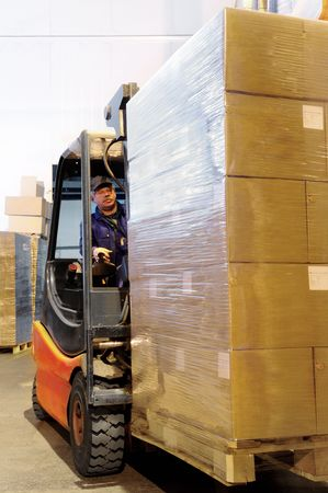 pallets: Worker driver of a forklift loader in blue workwear at warehouse with cardboard boxes on pallet