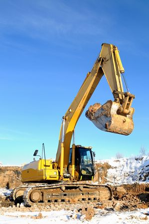 Yellow excavator loader at construction site with raised bucket in winter Stock Photo - 6419159
