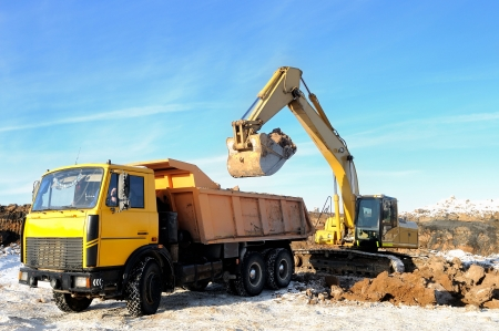 Excavator loading dump truck tipper at open cast over blue sky in winter photo