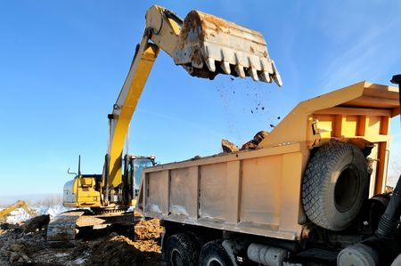 tipper: Loader Excavator loading body of a dump truck tipper at open cast over blue sky in winter