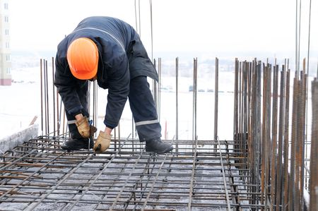 concrete form: worker in workwear making reinforcement metal framework for concrete pouring Stock Photo
