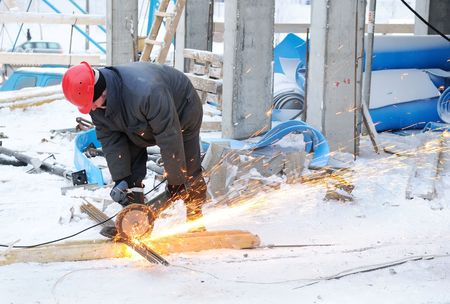 abrasive: worker in workwear cutting metal reinforcing bar with abrasive cutoff saw disk Stock Photo