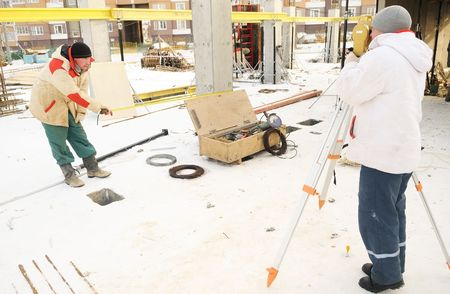 exact position: Land surveyor and assistant working with theodolite equipment at a construction site in winter