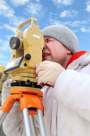 exact position: Land surveyor working with theodolite equipment at a construction site in winter over blue sky