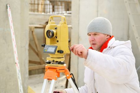 geodesist: Land surveyor working with theodolite equipment at a construction site in winter over blue sky