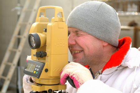 Land surveyor working with theodolite at a construction site photo
