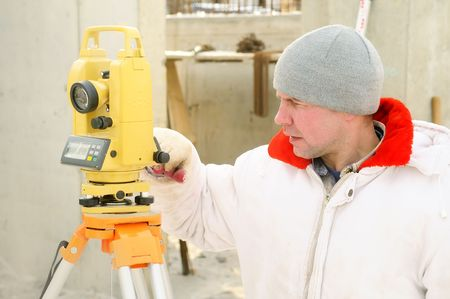 Land surveyor working with theodolite equipment at a construction site in winter over blue sky photo