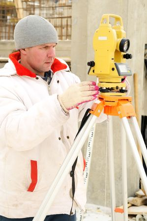 geodesist: Land surveyor and equipment theodolite at a construction site in winter