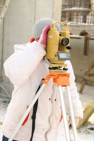 exact position: Land surveyor and equipment theodolite at a construction site in winter