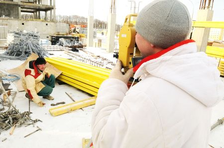 Land surveyor working with theodolite equipment at a construction site in winter photo