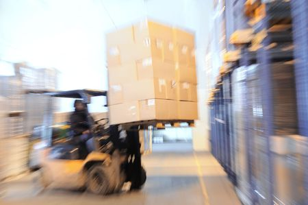 warehouse equipment: Electric forklift in warehouse loading cardboard boxes. Intentional optical zooming blur