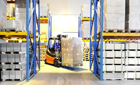 forklift driver: Worker driver of a forklift loader in blue workwear at warehouse with cardboard boxes on pallet