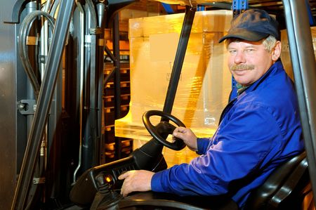 Worker driver of a forklift loader in blue workwear at warehouse Stock Photo - 6419162