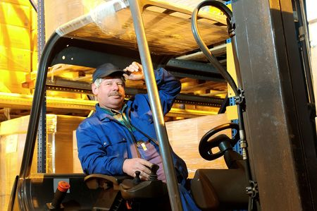Worker driver of a forklift loader in blue workwear at warehouse Stock Photo - 6419161