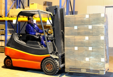 work load: Worker driver of a forklift loader in blue workwear at warehouse with cardboard boxes on pallet