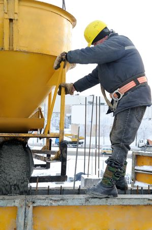 construction building worker at construction site pouring concrete in mould photo