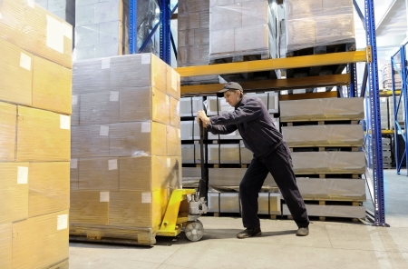 moving crate: worker with fork pallet truck stacker in warehouse loading Group of cardboard boxes Stock Photo