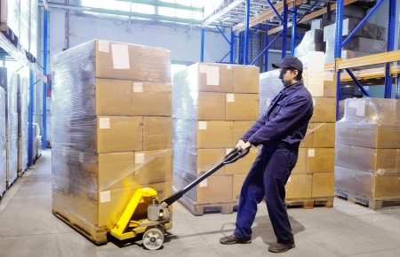 warehouse equipment: worker with fork pallet truck stacker in warehouse loading Group of cardboard boxes Stock Photo
