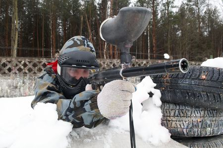 paintball sport player with mask aiming gun and shooting to enemy in winter photo
