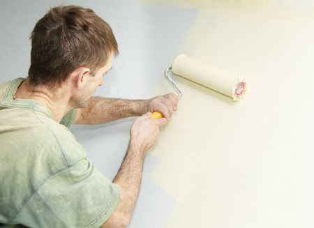 Painter worker hand at decoration work painting a wall with roller photo