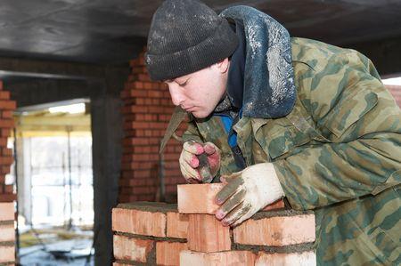 paredes de ladrillos: manos de un alba�il de trabajador de alba�il de construcci�n haciendo una obra de f�brica con paleta