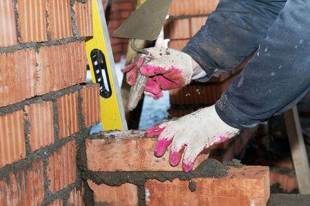 paredes de ladrillos: manos de un alba�il de trabajador de mason de construcci�n haciendo una obra de f�brica con paleta