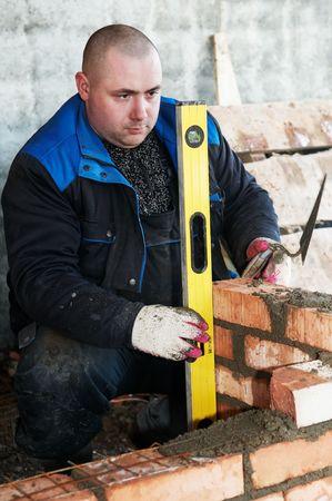 paredes de ladrillos: alba�il de trabajador de construcci�n alba�il comprobaci�n de una obra de f�brica con tubo de nivel