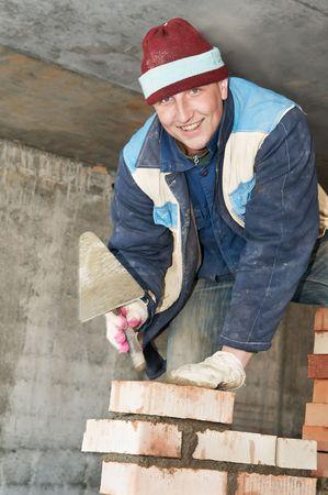 hands of a construction mason worker bricklayer making a brickwork with trowel Stock Photo - 6501755