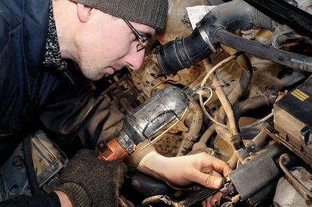 repairman mechanic worker at car repairing work photo