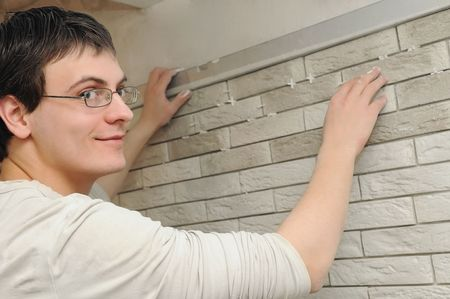 young worker tiler laying a tile on wall and using level Stock Photo - 6786794
