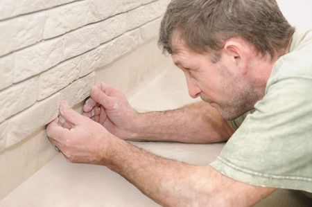 worker mason tiler laying a decoration tile on wall photo