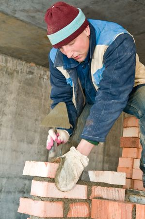 mason worker bricklayer making a brickwork with trowel Stock Photo - 7156213