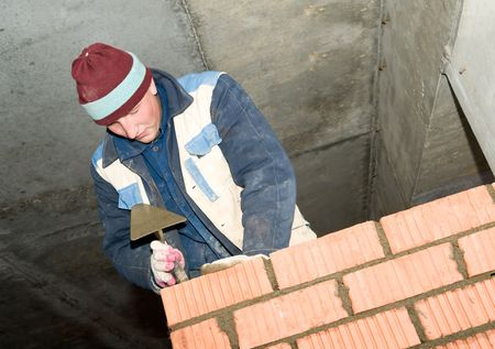 construction mason worker bricklayer making a brickwork with trowel photo