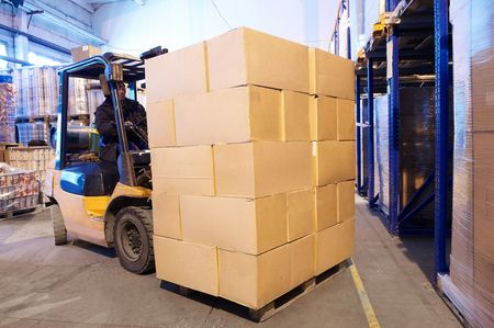 Worker driver of a forklift loader at warehouse loading cardboard boxes on pallet to shelves photo