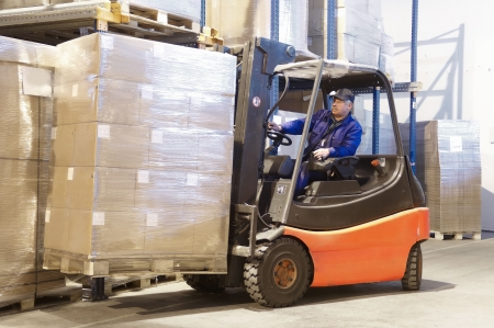 Forklift loader worker driver at warehouse photo