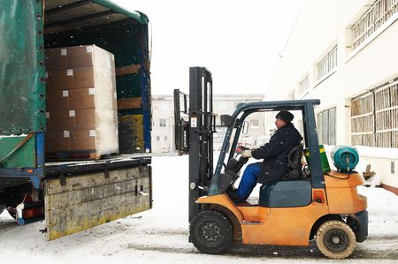 warehouse forklift loader loading cardboard boxes into a car outdoors photo