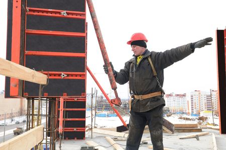 construction worker builder ruling during formwork installation for concrete filling photo