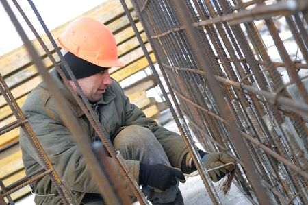 worker in workwear making reinforcement metal framework lattice for concrete pouring photo