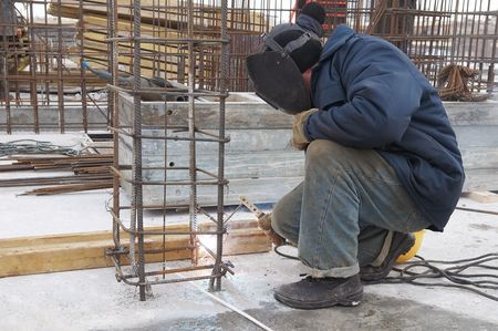 electrode: worker welding by electrode a metal lattice reinforcement for concrete pouring Stock Photo